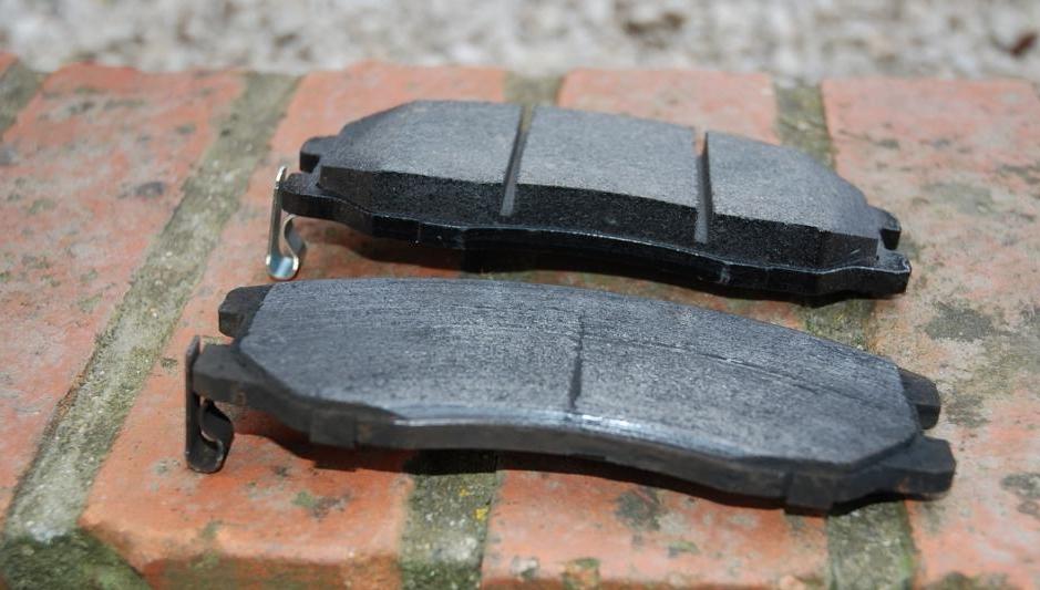 Photo montrant une plaquette de frein neuve et une plaquette de frein usée